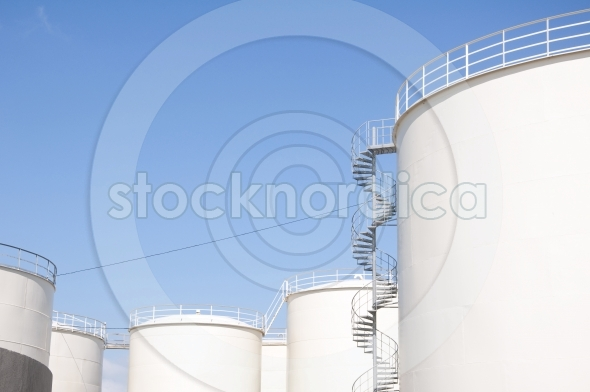 Industrial oil tanks clear blue sky background